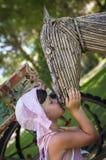 Muchacha que besa a la cabeza de caballo de madera  Fotos de archivo
