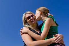 Muchacha que besa a la madre Foto de archivo