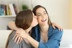 Muchacha que besa a su amigo en un sofá en casa Fotos de archivo