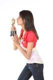 Muchacha que besa su trofeo del oro imágenes de archivo libres de regalías
