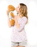 Muchacha que besa un oso de peluche Fotos de archivo