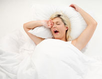 Muchacha que bosteza en cama después de dormir Imagenes de archivo