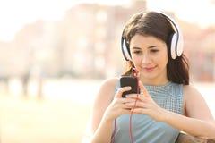 Muchacha que busca canciones y música que escucha con los auriculares Imagen de archivo