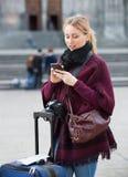 Muchacha que busca para la dirección usando su teléfono en ciudad Imágenes de archivo libres de regalías