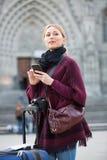 Muchacha que busca para la dirección usando su teléfono en ciudad Fotos de archivo
