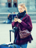 Muchacha que busca para la dirección usando su teléfono en ciudad Fotografía de archivo