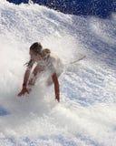 Muchacha que cae mientras que practica surf Foto de archivo