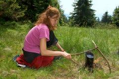 Muchacha que calienta el agua Fotografía de archivo libre de regalías