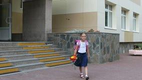 Muchacha que camina abajo de las escaleras con el ramo de la mochila y de las flores de la puerta de la escuela De nuevo a concep Imagenes de archivo