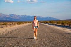 Muchacha que camina abajo del camino sin fin por el Death Valley Imagenes de archivo