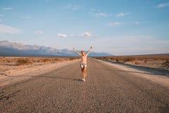Muchacha que camina abajo del camino sin fin por el Death Valley Fotos de archivo libres de regalías
