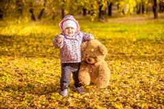 Muchacha que camina con el oso de peluche en el parque del otoño Foto de archivo