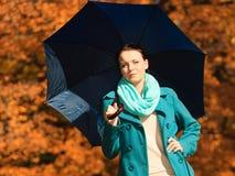 Muchacha que camina con el paraguas azul en parque otoñal Imagenes de archivo