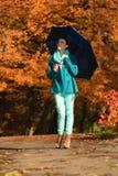 Muchacha que camina con el paraguas azul en parque otoñal Imagen de archivo