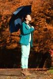 Muchacha que camina con el paraguas azul en parque otoñal Imagen de archivo libre de regalías