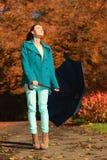 Muchacha que camina con el paraguas azul en parque otoñal Imágenes de archivo libres de regalías