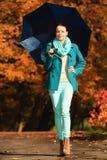 Muchacha que camina con el paraguas azul en parque otoñal Fotografía de archivo
