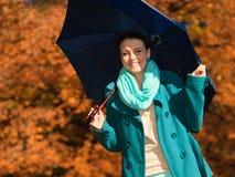 Muchacha que camina con el paraguas azul en parque otoñal Foto de archivo libre de regalías