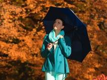 Muchacha que camina con el paraguas azul en parque otoñal Foto de archivo