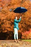 Muchacha que camina con el paraguas azul en parque otoñal Fotografía de archivo libre de regalías