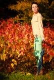 Muchacha que camina con el paraguas en parque otoñal Fotografía de archivo libre de regalías
