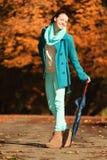 Muchacha que camina con el paraguas en parque otoñal Imagenes de archivo