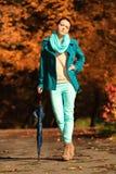 Muchacha que camina con el paraguas en parque otoñal Fotos de archivo