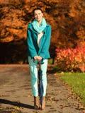 Muchacha que camina con el paraguas en parque otoñal Imagen de archivo