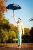 Muchacha que camina con el paraguas en parque otoñal Imagen de archivo libre de regalías