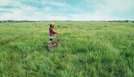 Muchacha que camina con la bicicleta en verano Foto de archivo