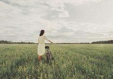 Muchacha que camina con una bicicleta en prado del verano imagen de archivo
