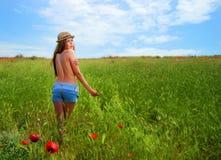 Muchacha que camina en campo de la amapola Fotografía de archivo