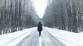 Muchacha que camina en el camino al bosque del invierno almacen de metraje de vídeo