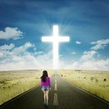Muchacha que camina en el camino con una cruz Foto de archivo libre de regalías