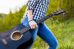 Muchacha que camina en el campo con una guitarra a disposición Imagen de archivo libre de regalías