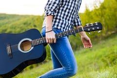 Muchacha que camina en el campo con una guitarra a disposición Foto de archivo libre de regalías