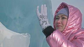 Muchacha que camina en el hielo agrietado de un lago Baikal congelado El viajero de la mujer explora y mira una masa de hielo flo metrajes
