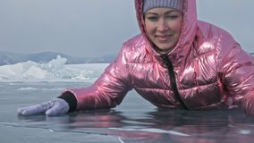 Muchacha que camina en el hielo agrietado de un lago Baikal congelado El viajero de la mujer explora y mira una masa de hielo flo almacen de metraje de vídeo