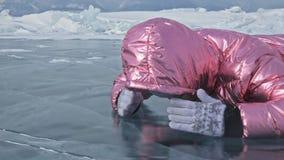 Muchacha que camina en el hielo agrietado de un lago Baikal congelado El viajero de la mujer explora y mira una masa de hielo flo almacen de video