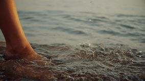 Muchacha que camina en la arena mojada de la línea de la playa Las piernas de la mujer joven que van a lo largo del océano varan  almacen de video