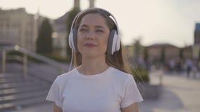 Muchacha que camina en la ciudad, madrugada de la calma mujer en auriculares grandes con una taza de papel 4K almacen de metraje de vídeo