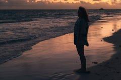 Muchacha que camina en la costa del océano por mañana Foto de archivo libre de regalías