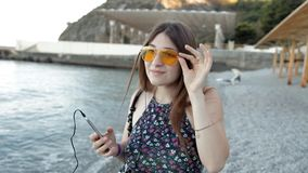 Muchacha que camina en la playa que escucha la música y el baile almacen de video