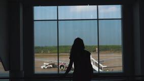 Muchacha que camina en la ventana en el terminal de aeropuerto almacen de video