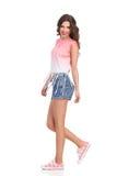 Muchacha que camina en pantalones cortos y zapatillas de deporte de los vaqueros Imagen de archivo libre de regalías