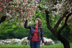 Muchacha que camina en parque floreciente Imagen de archivo