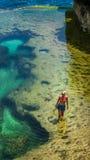 Muchacha que camina en piscina amarilla natural en Cliff Formation hermoso, lugar extraño, Nusa Penida Bali Indonesia Fotografía de archivo libre de regalías