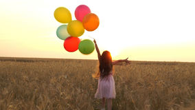 Muchacha que camina en un campo con los globos imagen de archivo