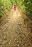 Muchacha que camina en un pequeño camino del campo Imágenes de archivo libres de regalías