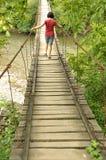 Muchacha que camina en un puente de madera sobre un río Fotografía de archivo libre de regalías